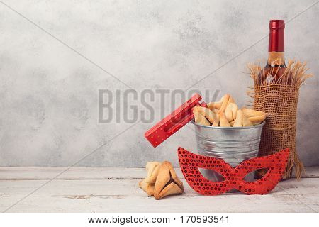 Jewish holiday Purim concept with hamantaschen cookies or hamans ears carnival mask and wine bottle over rustic background