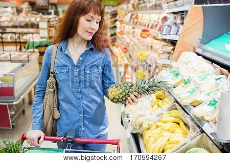 Customer choosing a pineapple in a supermarket