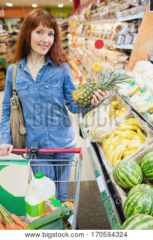 Smiling customer holding a pineapple in a supermarket