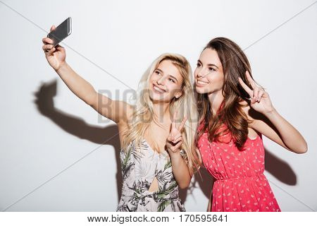 Portrait of a happy two smiling girls making selfie photo on smartphone and showing two fingers sign on white background