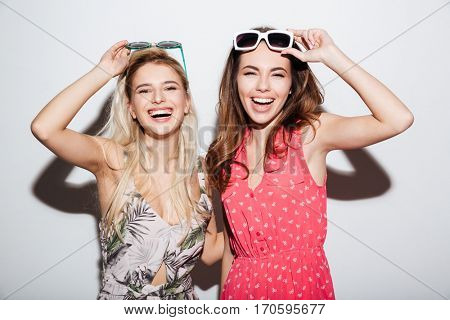Portrait of two cheerful pretty girls wearing dresses and glasses isolated on a white background