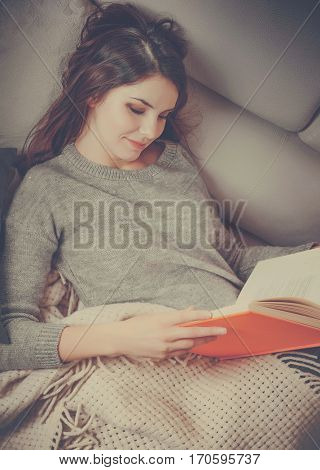 Pretty young girl reads a book. Lying at white sofa with wrap and pillows in modern interior room home. Sunny day warm light from window. Happy people lifestyle concept. Vintage colors