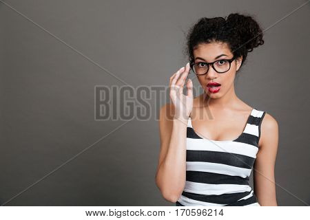 Surprised african american young woman in glasses standing with opened mouth over grey background