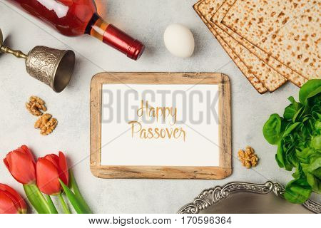 Passover holiday concept seder plate matzoh and photo frame on bright background. Top view from above