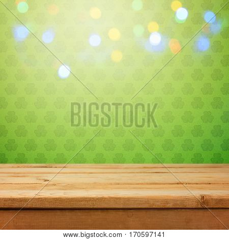 Empty wooden deck table over green shamrock wallpaper background with bokeh lights overlay. St. Patricks day concept for product monatge display