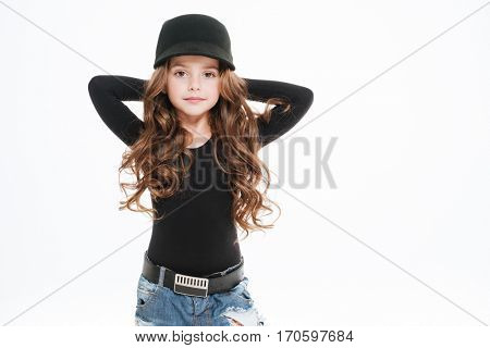 Beautiful curly little girl in hat standing with hands behind head over white background