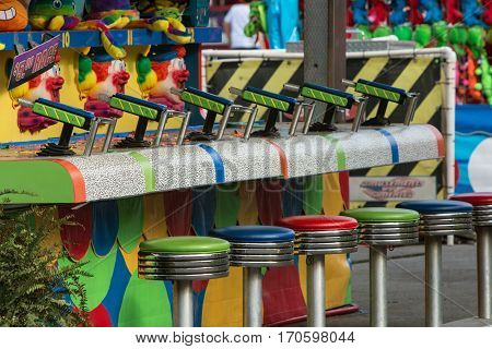 LAWRENCEVILLE, GA - SEPTEMBER 2016: Empty stools and squirt guns await contestants at a game at the Gwinnett County Fair in Lawrenceville GA on September 17 2016.