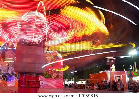 LAWRENCEVILLE, GA - SEPTEMBER 2016:  Motion blur shows colorful streaking lights of fast-moving carnival ride at the Gwinnett County Fair in Lawrenceville GA on September 17 2016.