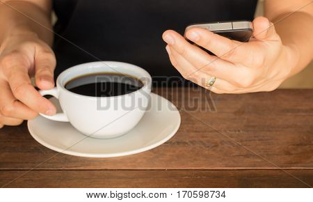 Hand on coffee cup and smartphone stock photo