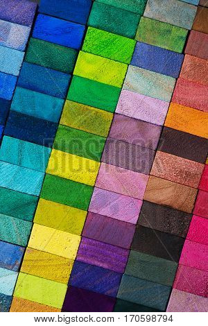 Spectrum of multi colored wooden blocks aligned. Background or cover for something creative or diverse.