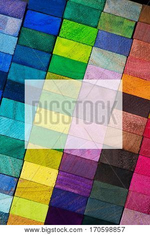 Cover for creative works. Spectrum of multi colored wooden blocks with blank semi-transparent white area. Background or cover for something creative or diverse.