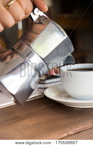 Hand on traditional italian moka pot stock photo