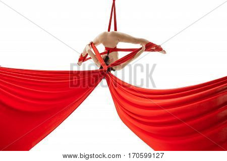 Pretty woman - aerial acrobat doing acrobatic tricks on red silks.  Young flexible aerialist performing on white isolated studio background