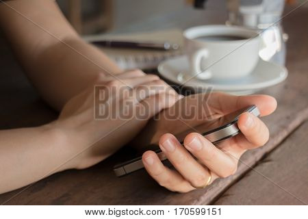 Hand on smartphone at wooden table stock photo