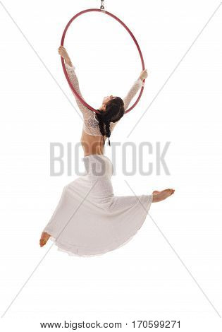 Rear view of aerial acrobat doing acrobatic tricks with ring.  Young flexible aerialist performing with hoop on white isolated studio background