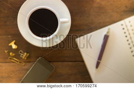 Hot cup of coffee on wooden work table stock photo