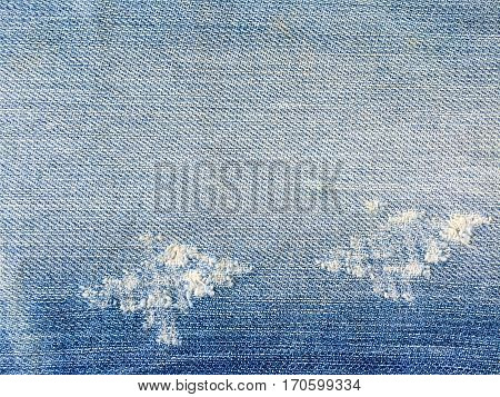 Close up of destroyed torn denim jeans background and texture