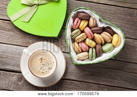 Colorful macaroons in Valentines day heart shaped gift box and coffee cup on wooden table. Top view