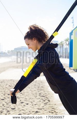 Woman training with TRX straps by the beach