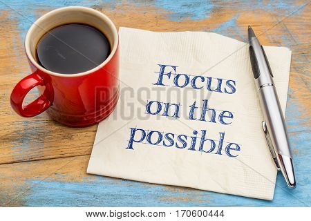 Focus on the possible - motivational handwriting on a napkin with a cup of coffee