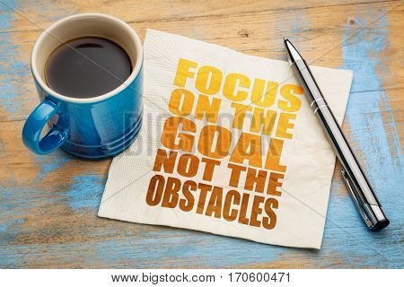 Focus on the goal, not obstacles - word abstract  on a napkin with a cup of espresso coffee