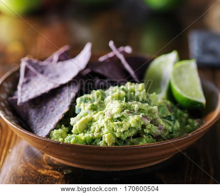 colorful blue corn tortilla chips with fresh mexican guacamole and lime wedges