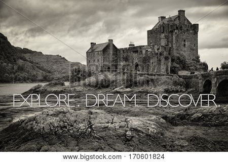 inspirational quote saying Explore, dream, discover on Eilean Donan Castle in black and white at low tide in the Highlands, Scotland