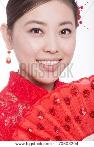 young asian woman in red cheongsam holds paper fan in chinese new year