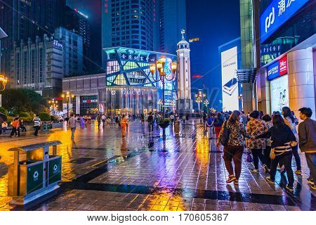 Chongqing China - September 18 2015: At Night People walking in downtown business center of Chongqing Chongqing is the largest direct-controlled municipality and comprises 19 districts 15 counties and 4 counties.
