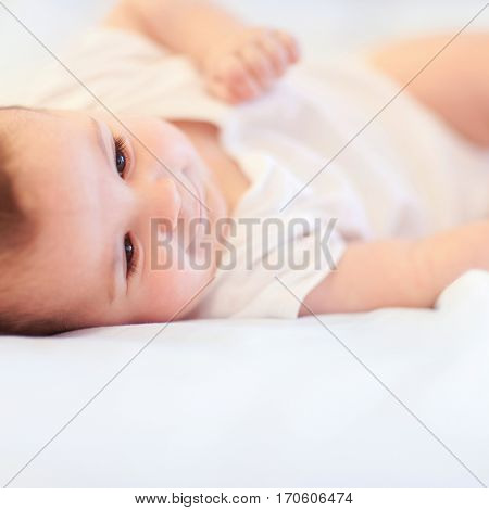 Close up portrait of cute baby. Fun happy baby in bedroom. Family morning at home. Child relaxing on white bed. Textile and bedding for kids.