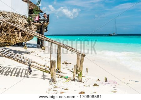 beautiful clean ocean beach with wooden footway and a hut with ocean and sky on the background