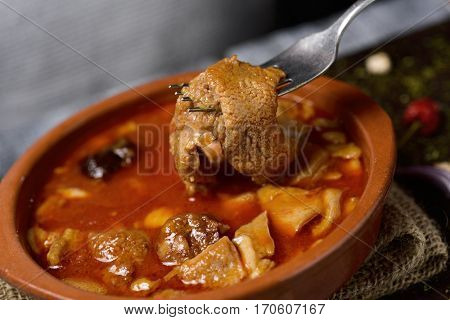 closeup of an earthenware bowl with spanish callos, a typical beef tripe stew with chickpeas, morcilla and chorizo, on a rustic wooden table