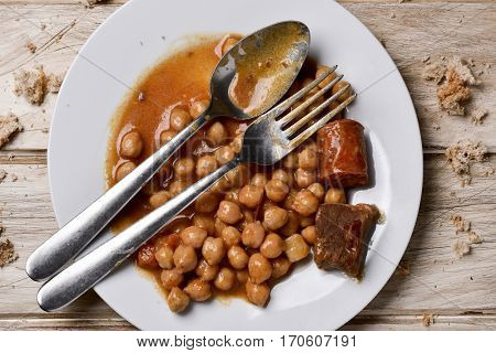 high-angle shot of a plate with remains of chickpea stew and remains of bread, on a white rustic wooden table