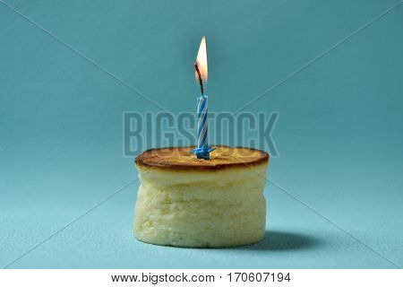a cheesecake topped with a lit birthday candle on a blue background