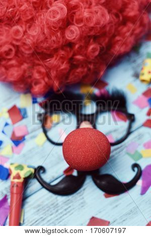 a red wig, a pair of fake black glasses with eyebrows, a red clown nose and a mustache forming the face of a man on a blue rustic wooden surface full of confetti