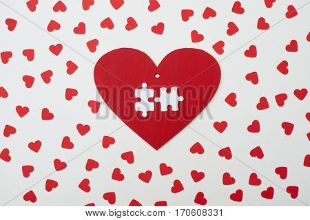 Top view of red heart with two white puzzle encircled with small hearts. Love symbol. Valentine day