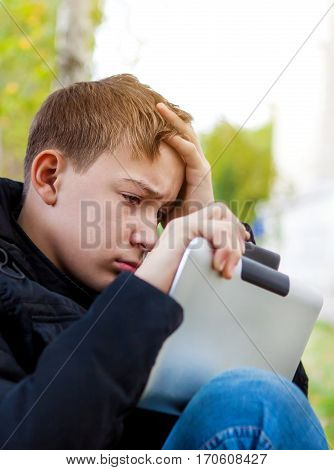 Sad Kid with Tablet Computer in the Park