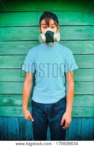 Vignetting Photo of Teenager Portrait in the Gas Mask on the Wooden Wall Background