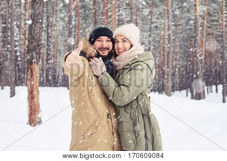 Mid shot of happy married couple in the forest. Cheer couple look embrace over a picturesque wintry forest. Cheer husband showing thumb up and embraces wife over a picturesque wintry forest