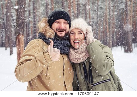 Close-up of exhilarated husband with thumb up hugging wife during the snowfall in the forest. Looking at the camera and holding thumbs up. Hugging each other and posing at the camera
