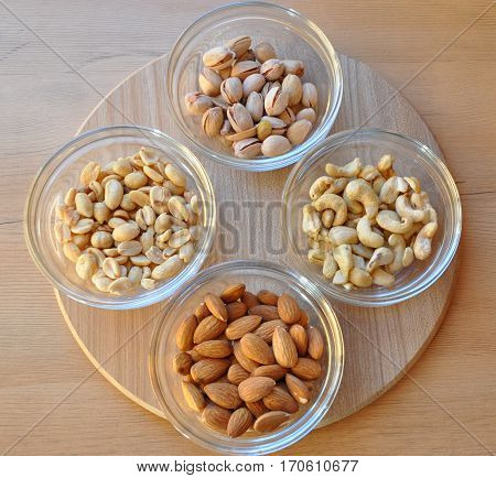 nuts, dry, peanuts, almonds, cashews, pistachios, set in the dishes, diet, food, health, natural, organic, vegetarian