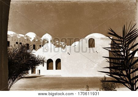 retro photo, on which image of palm trees near white structure in Egypt