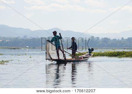 INLE LAKE, MYANMAR - DECEMBER 26, 2016: Two Burmese fisherman in traditional wooden boat. Inle Lake, Myanmar