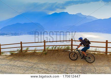Mountain biking  man at sunrise over Lake Garda on path Sentiero della Ponale, Riva del Garda, Italy