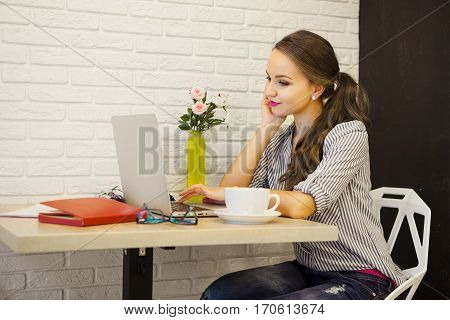 Young girl sitting at table and looking into laptop monitor with white cup of drink. Female has beautifully make-up, dressed in striped shirt and jeans. Mysterious and romantic person