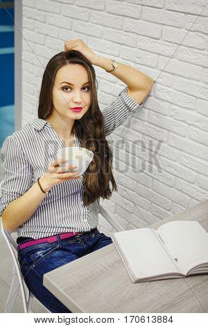 Woman sitting at table drinking coffee or tea. Girl in casual cloth put hand on head leaning on brick wall. Confident girl have rest. Open diary with pen on the desk. Having break during work