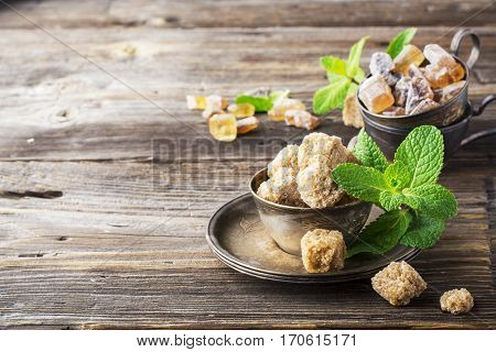 Lump brown cane sugar in a vintage metal dishes with a sprig of fresh mint on a simple wooden background. The concept of natural organic food. selective