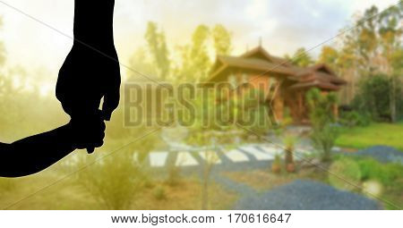Silhouette children's hand and adult hand holding together over blur background of new wood house, dreaming about home, real estate and family concept
