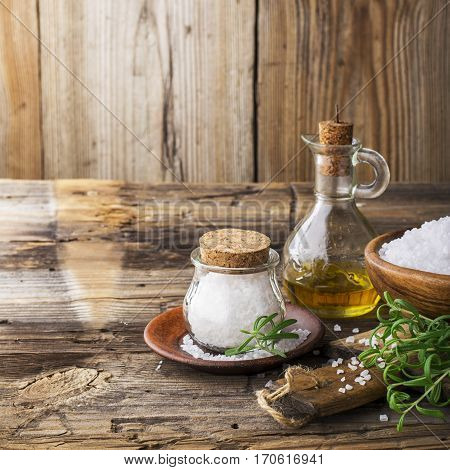 Sea salt and green rosemary on the wooden table, selective focus