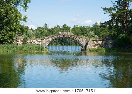 Old Humpback bridge on White lake, sunny day in July. Gatchina